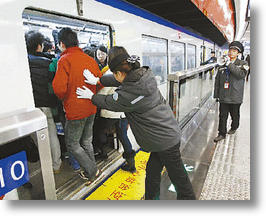 Paid 'People Pushers' Press Passengers on China's Subways