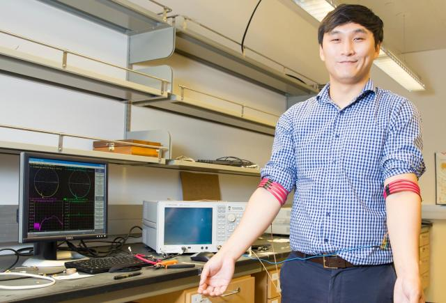 Prototypical magnetic communication coils: graduate student Jiwoong Park demonstrates magnetic field human body communication. Image from UC San Diego.