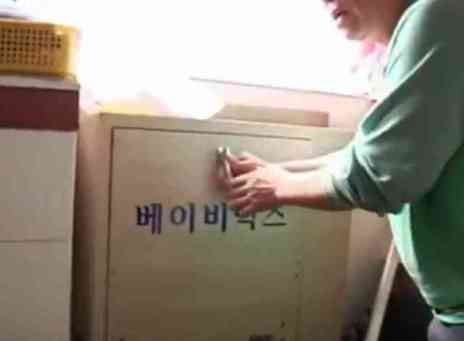 Lee Jong-Rak retrieving a baby from the drop box (You Tube Image)