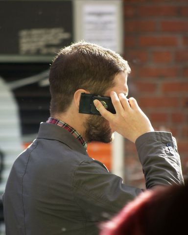 A Man Using His Cell Phone (Image by Tim Parkinson/Creative Commons via Wikimedia)
