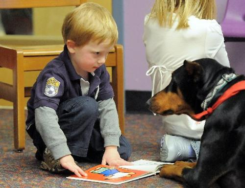 Child checks with the dog to makes sure she understands....: image via kgnu.org of child in Bloomfield, CO library